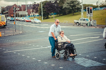 man pushing  a woman in a wheel chair
