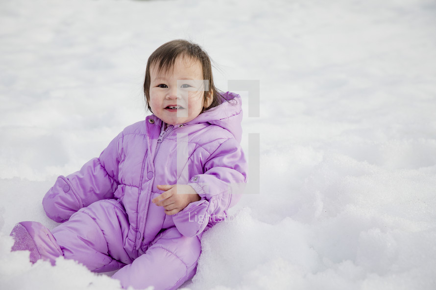 a baby playing in snow