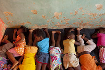 African children napping on a mat.