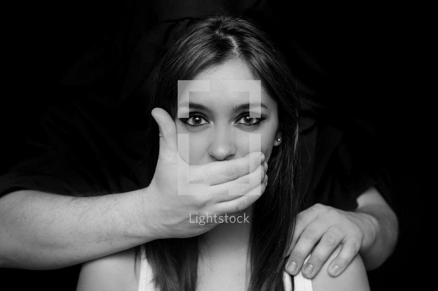Hear no evil; speak no evil. A woman with her mouth and ear covered by a man's hands.