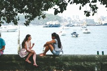 women sitting on a wall in conversation near a harbor