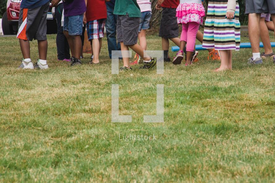 children's legs and feet in grass