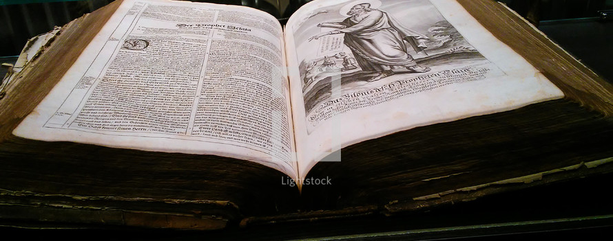 An Old Bible Manuscript fully illustrated with wood carving, etchings, illustrations and old english type face font printed on an old manual printer.