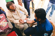 healthcare and medicine - man getting his blood pressure checked
