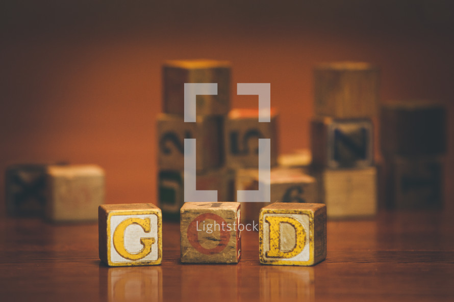 pile of wood blocks on a playroom floor and the word God