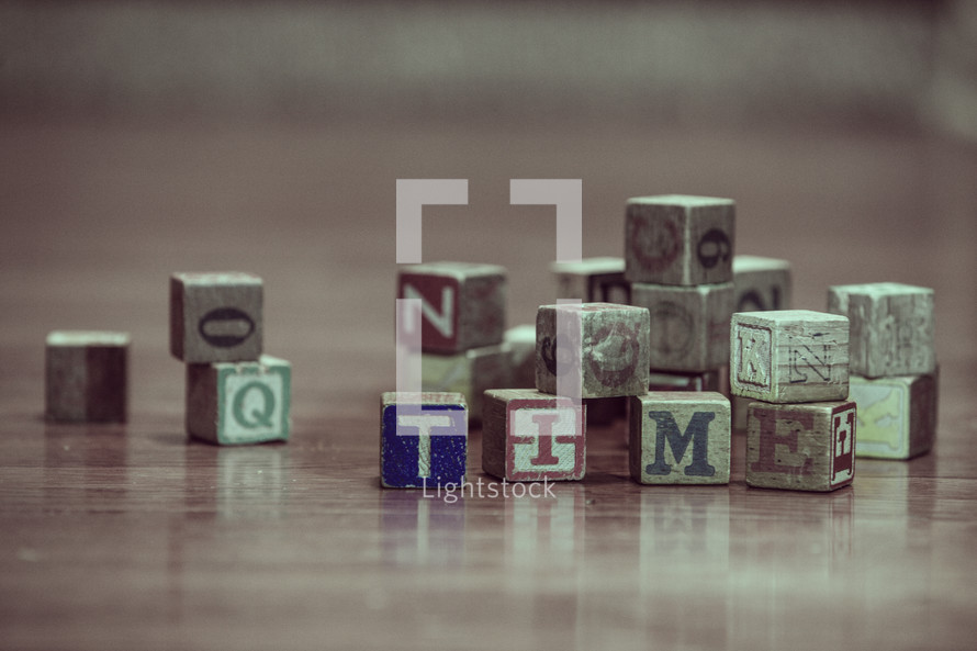 pile of wood blocks on a playroom floor and the word time