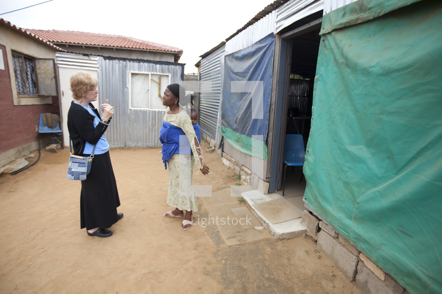 women in conversation in a shanty town