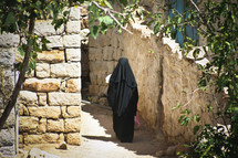 A woman in a burka walking through the streets of Yemen