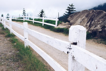 white fence along a dirt road
