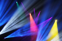 spotlights and stage lights illuminating a vivid colorful background