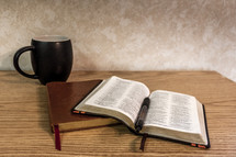 Bible open on desk with journal and black coffee cup