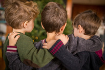 brothers hugging in front of a  Christmas tree