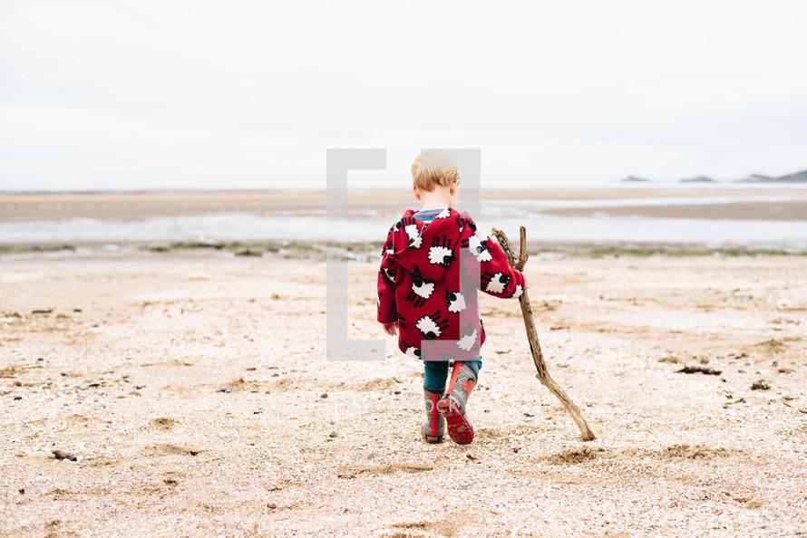 a boy child in rain boots dragging a stick on a beach