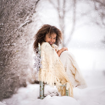 a little girl wrapped in a blanket in the snow