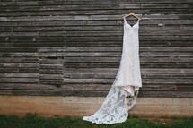 wedding dress hanging on weathered wood siding