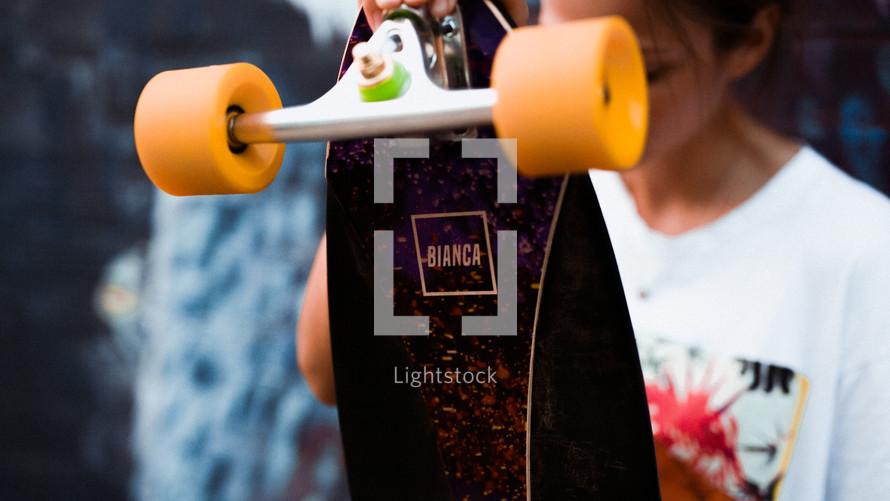 a woman holding a skateboard