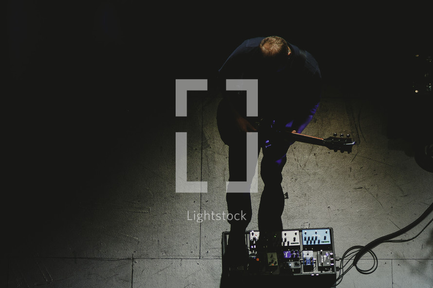 a musician on stage with guitar and foot pedals