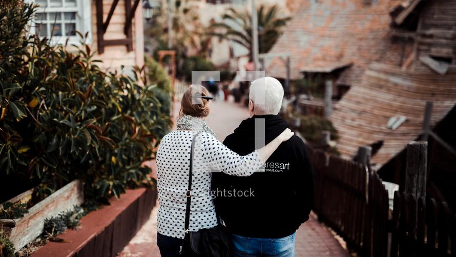 couple walking through a village