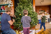 father and son's decorating a Christmas tree