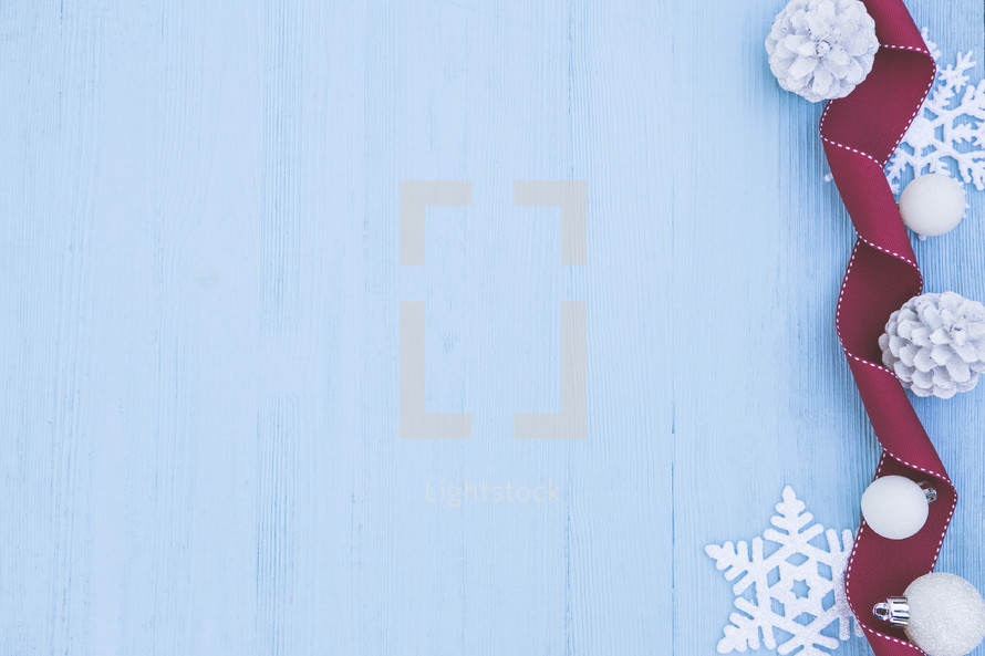 red ribbon, snowflake, pine cones, and ball ornaments border on light blue