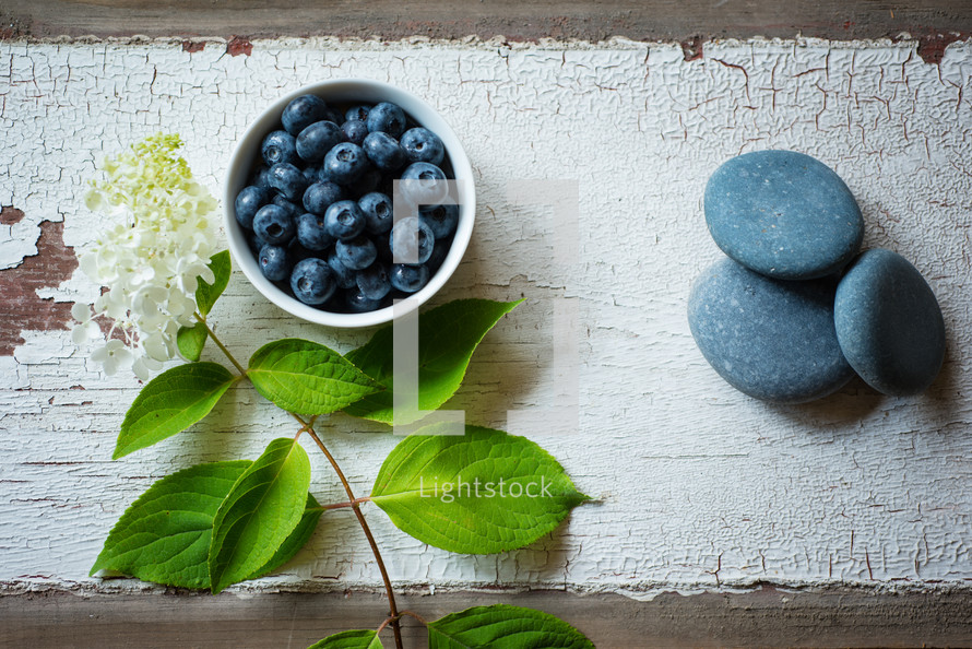 bowl of blueberries and flowers on wood