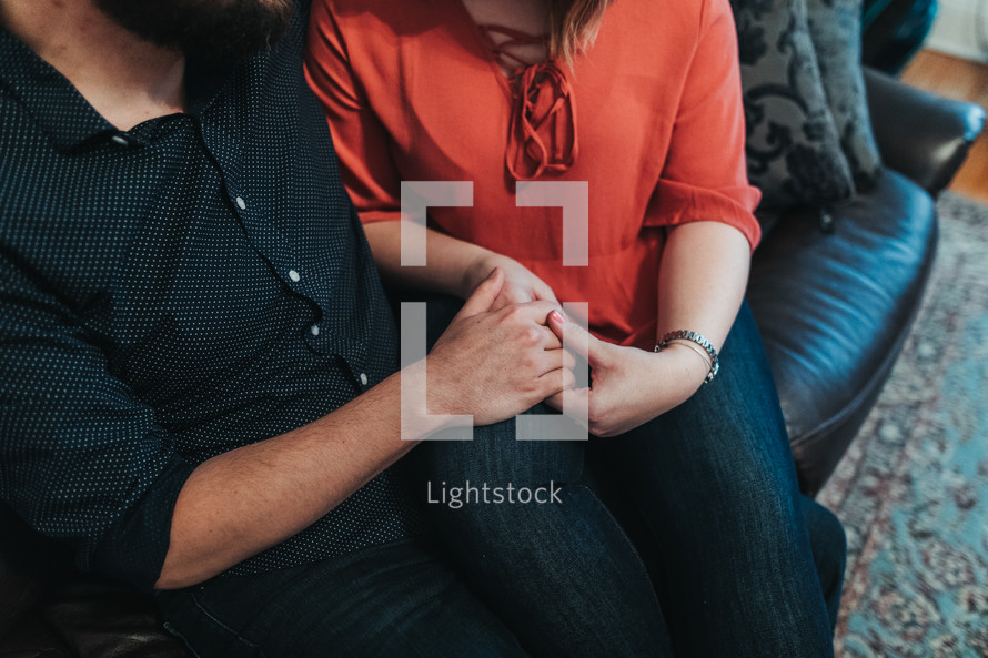 a couple sitting on a couch holing hands