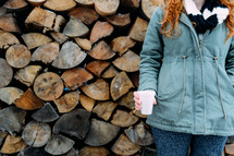 woman in a winter coat standing next to a stack of firewood