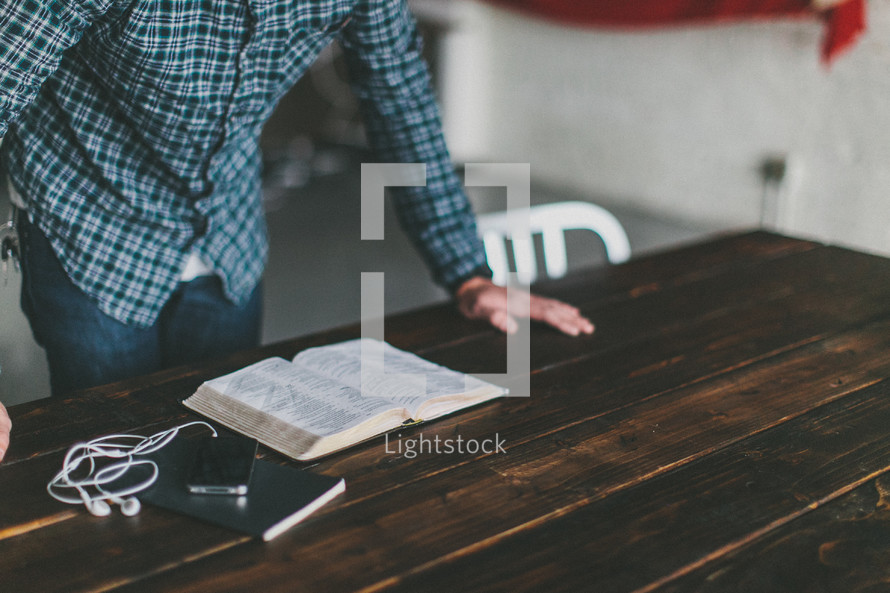 man resting his hands on a table reading a Bible with an ipod nearby