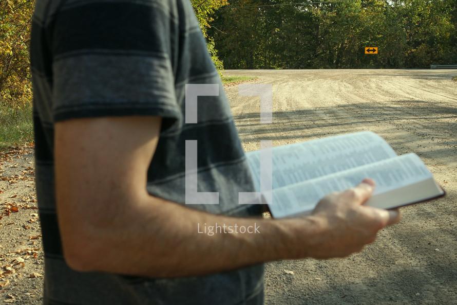 arrow street sign and a man reading a Bible