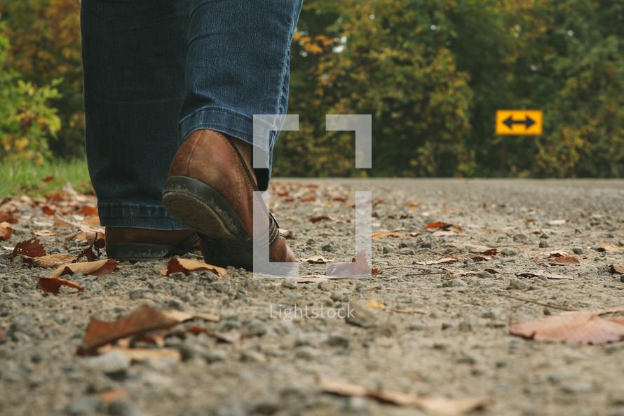arrow street sign and feet