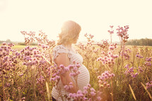 pregnant woman standing in a field of wildflowers
