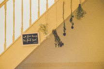 A Bible verse and dried flowers hanging from a staircase.