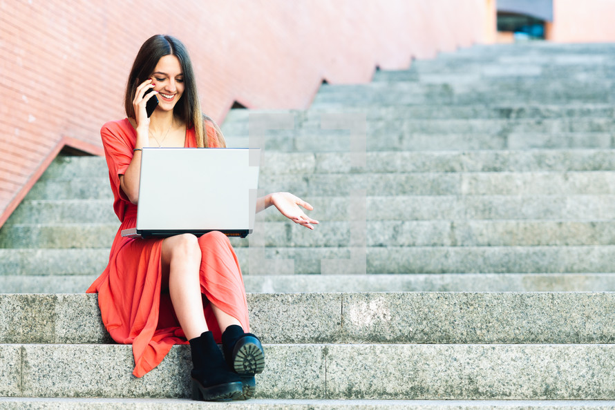 young woman sitting on outdoors stairs wearing red dress with a laptop
