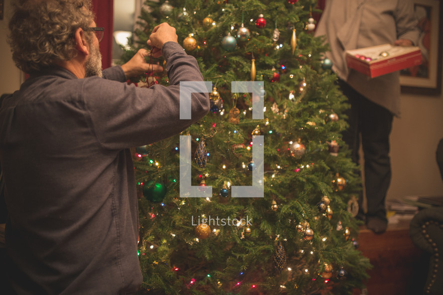 a man decorating a Christmas tree