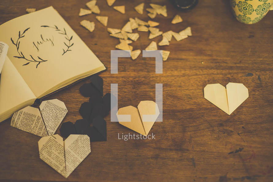 Paper hearts on a wooden table.