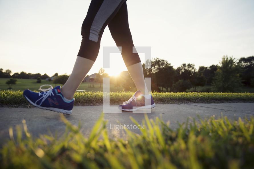 feet of a woman walking on a sidewalk.