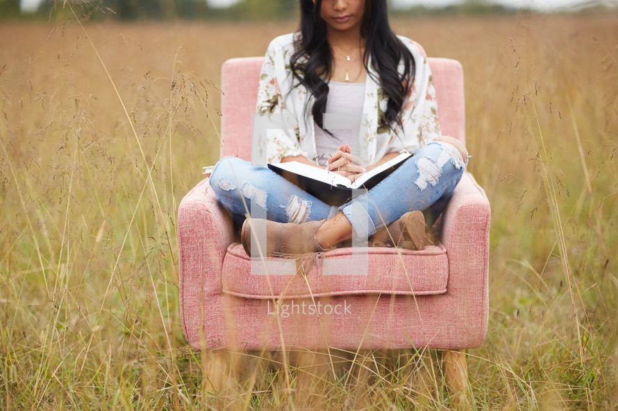 a young woman sitting in a chair in a field reading a Bible and praying