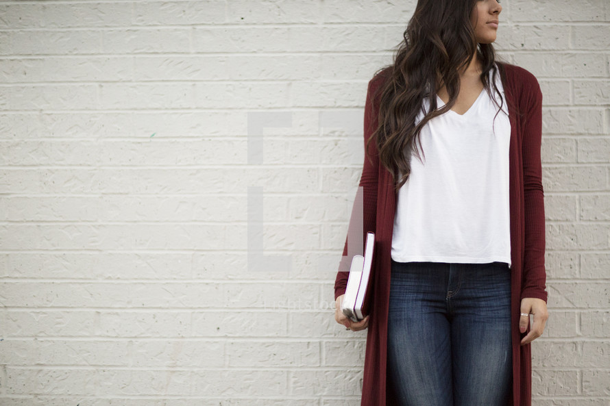a young woman standing in front of a white wall holding a Bible and journal