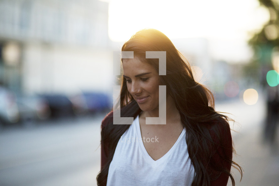 a young woman walking down a sidewalk at sunset