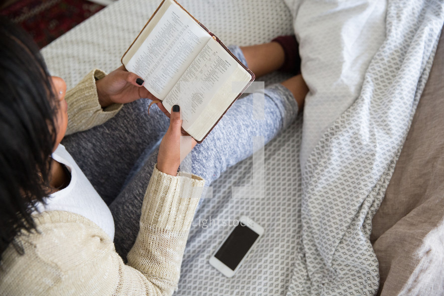young woman sitting in bed reading a Bible