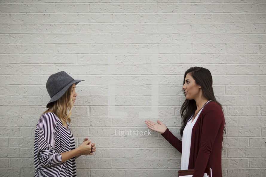 friends standing in front of a white wall with one holding a Bible and journal talking, inviting a friend to join a Bible study