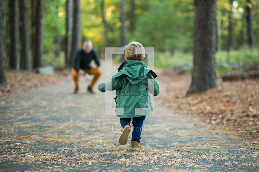 a toddler boy running to his father outdoors
