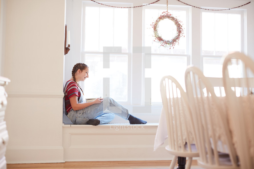 girl sitting in a window seat reading a book