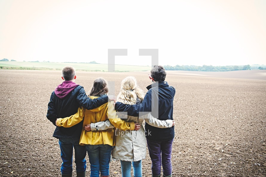 teens standing together in a field with backs to the camera