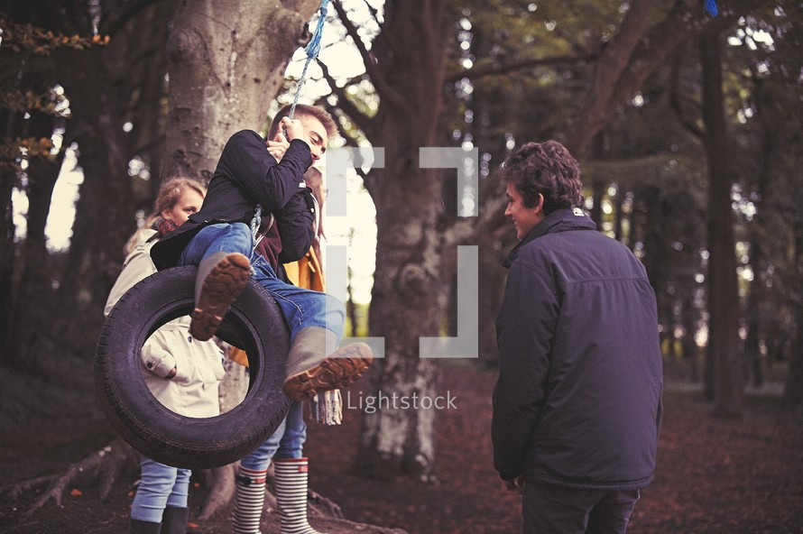 teens playing on a tire swing