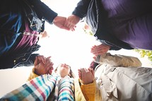 teens holding hands in a prayer circle