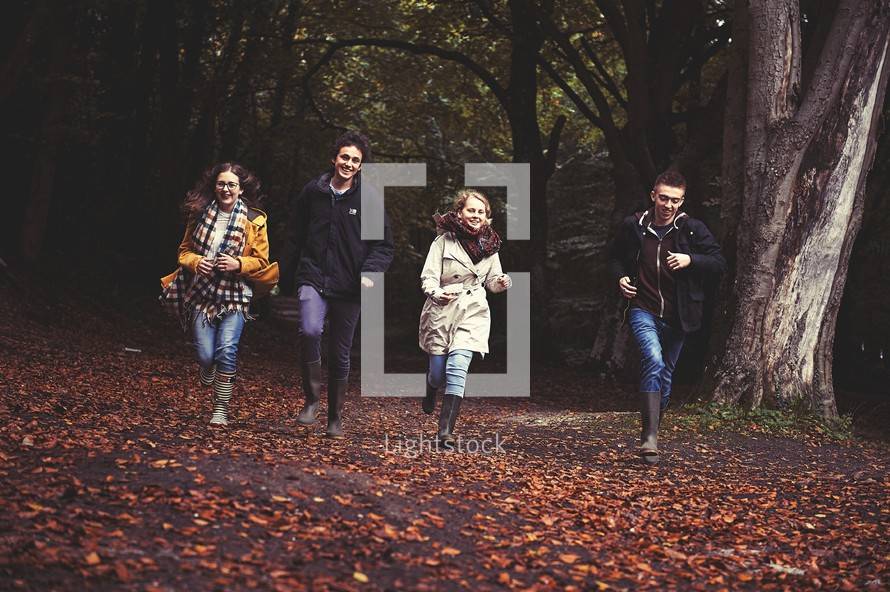 youth running through fall leaves