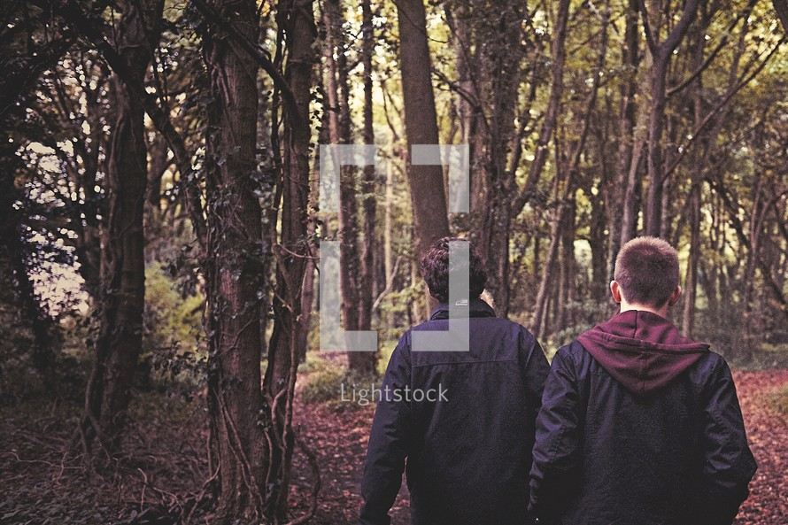 teen boys walking through a forest