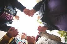 teens holding hands in prayer