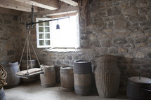 Baskets, barrels, and a pulley in a stone room with wooden floor.